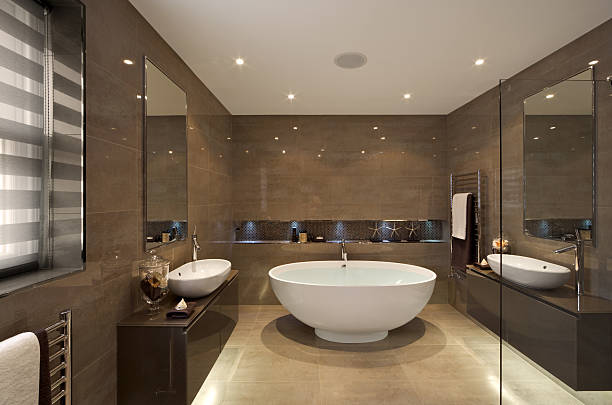 A beautifully designed bathroom in an expensive new home that has been dressed by a leading Interior Designer. A white oval bath sits in the centre full of water with a tap flowing. White and brown towels on the towel rails match the bronze tilework and stone floor. A his and hers basin sit on either side of the room.